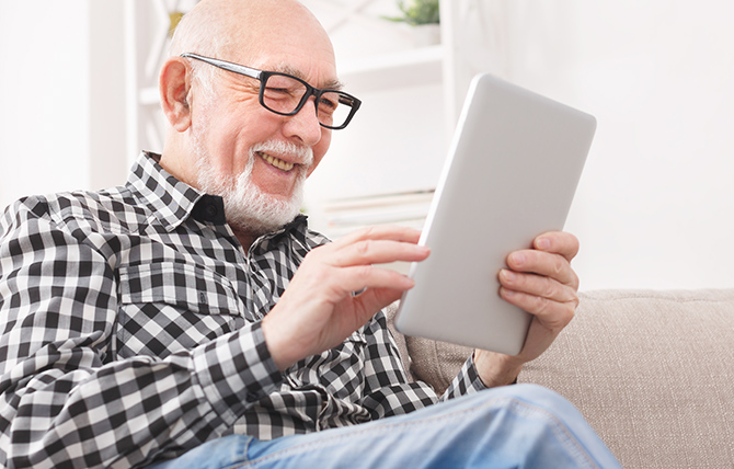 A man holding and looking at a tablet